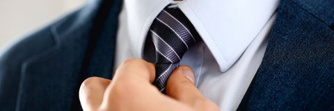 Male arm in blue suit set tie closeup. White collar management job serious move secretary student luxury formal interview executive agent marriage store Stock Photo