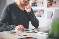 Male arm demonstrating image at desk. Focus on close up hand of serene bearded men showing on picture while situating at table in office. Labor concept Stock Photo