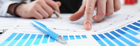 Male arm hold silver pen and point finger in financial graph stock images