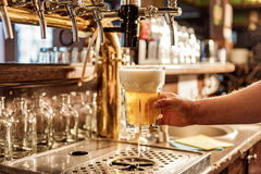 Male arm keeping pouring beer in alehouse Royalty Free Stock Images