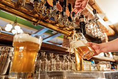 Male arm pouring beer in tap-room Royalty Free Stock Image