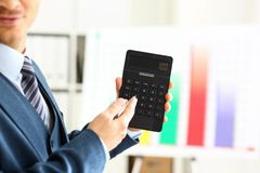 Male arm in suit hold calculator pressing buttons. In office closeup. Electronic keypad math data invest credit debit research mortgage loan money saving Stock Photo