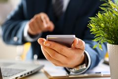 Male arm in suit hold phone. And silver pen at workplace closeup. Read news mania send sms chat addict use electronic bank modern lifestyle job plan colleague Stock Photography