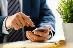 Male arm in suit hold phone and silver pen. At workplace closeup. Read news mania send sms chat addict use electronic bank modern lifestyle job plan colleague Royalty Free Stock Images