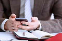 Male arm in suit hold phone and silver pen. At workplace closeup. Read news mania send sms chat addict use electronic bank modern lifestyle job plan colleague Royalty Free Stock Photography
