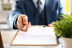 Male arm in suit offer contract form on clipboard. Pad and silver pen to sign closeup. Strike a bargain for profit white collar motivation union decision Royalty Free Stock Photo