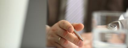 Male arm in suit and tie hold silver pen filling schedule stock photography