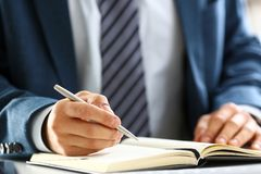 Male arm in suit and tie hold silver pen. Filling schedule in notepad at office workplace closeup. Legal law consult assistance gesture or finance investment Royalty Free Stock Photos