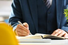 Male arm in suit and tie hold silver pen. Filling schedule in notepad at office workplace closeup. Legal law consult assistance gesture or finance investment Stock Images