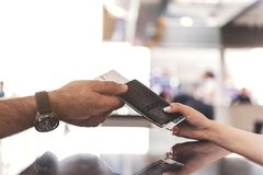 Male arm taking passport from young cashier. Focus on close up grandfather hand getting ticket on plane bound in booking office. Copy space Royalty Free Stock Images