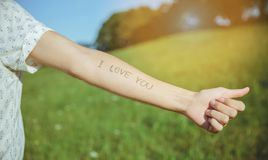 Male arm with text -I love you- written in skin. Closeup of male arm with the text -I love you- written in the skin over a sunny nature background Stock Photo