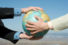 Male arms on earth globe. Male arms on terrestrial globe against landscape stock photos