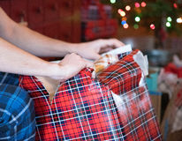 Male arms and hands opening Christmas present with blurry tree lights in background Stock Photography