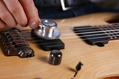 Male arms hold stethoscope head diagnosing guitar. Male arms hold stethoscope head fine diagnosing classic shape wooden guitar closeup. Six stringed school Stock Images