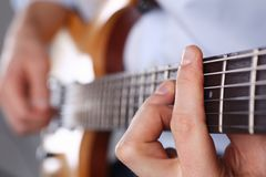 Male arms playing classic shape electric guitar. Male arms holding and playing classic shape wooden electric guitar closeup. Six stringed learning musical school Stock Image