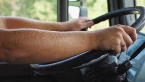Male arms of lorry driver holds a big steering wheel while driving a truck at sunny day. Trucker riding to destination