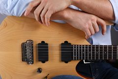 Male arms playing classic shape electric guitar. Male arms holding and playing classic shape wooden electric guitar closeup. Six stringed learning musical school Stock Photo