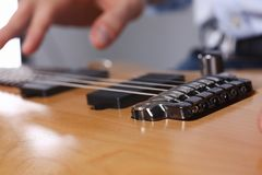 Male arms playing classic shape electric guitar. Male arms holding and playing classic shape wooden electric guitar closeup. Six stringed learning musical school Royalty Free Stock Image