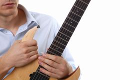 Male arms playing classic shape electric guitar. Male arms holding and playing classic shape wooden electric guitar closeup. Six stringed learning musical school Royalty Free Stock Photography
