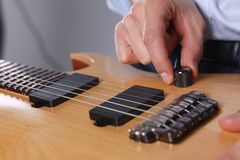 Male arms playing classic shape electric guitar. Male arms holding and playing classic shape wooden electric guitar closeup. Six stringed learning musical school Stock Photos