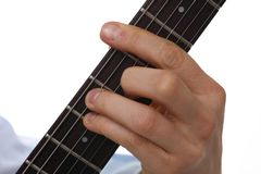 Male arms playing classic shape electric guitar. Male arms holding and playing classic shape wooden electric guitar closeup. Six stringed learning musical school Royalty Free Stock Photos