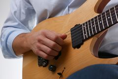 Male arms playing classic shape electric guitar. Male arms holding and playing classic shape wooden electric guitar closeup. Six stringed learning musical school Stock Photography