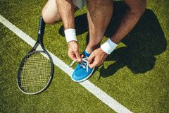 Male arms preparing boots for game. Close up man hands tying shoelaces on modern sneakers. Contemporary racket for tennis game situating near him. Healthy Stock Photos