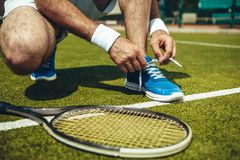 Man hands tying shoelaces on sneakers. Male arms preparing boots for play. Modern sport equipment situating near him. Training concept Royalty Free Stock Image