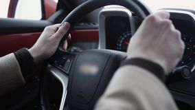 Male arms on steering wheel driving expensive car on bright day. Futuristic dashboard, close up stock footage