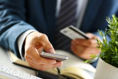 Male arms in suit hold credit card and phone. Make transfer closeup. Anti-fraud financial security when entering client discount program number or filling Royalty Free Stock Photo