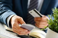 Male arms in suit hold credit card and phone. Make transfer closeup. Anti-fraud financial security when entering client discount program number or filling Royalty Free Stock Photos