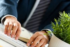 Male arms in suit typing on silver keyboard stock photo