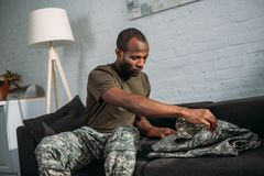 Male army soldier folding camouflage clothes. On sofa royalty free stock photography