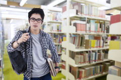 Male arrogant student in the library Royalty Free Stock Photo