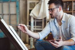 Male art school artist painting with oil on canvas Stock Photography