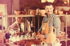 Male artisan in ceramic workshop. Cheerful smiling mature male artisan in apron holding ceramics in ceramics workshop royalty free stock photos