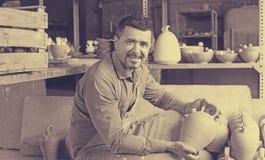 Male artisan in ceramic workshop. Cheerful smiling mature male artisan in apron posing in ceramics workshop stock photo