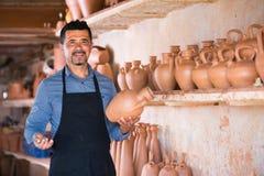 Male artisan in ceramic workshop. Joyful mature male artisan in apron holding ceramics in ceramics workshop stock photo