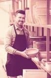 Male artisan in ceramic workshop. Smiling mature male artisan having ceramics in hands in ceramics workshop stock image