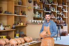 Male artisan in ceramic workshop. Smiling mature male artisan holding ceramics in ceramics workshop stock images