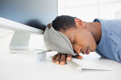 Male artist with head resting on keyboard in the office Royalty Free Stock Image