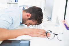 Male artist with head resting on keyboard Stock Image