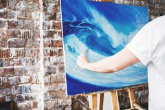Male artist hold paintbrush and drawing on canvas on ealse. Painter working in paint workshop. Art space Stock Photos