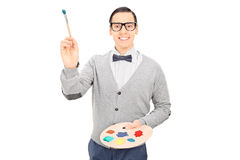 Male artist holding paintbrush and a color pallet Royalty Free Stock Photos