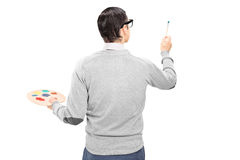 Male artist holding a paintbrush and color pallet. Isolated on white background, rear view royalty free stock photography