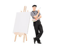 Male artist leaning on easel and holding a paintbrush Stock Images