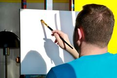 Male artist painter working in workshop with canvas on wood drawing board easel in art paint studio. Portrait of artist. royalty free stock photos