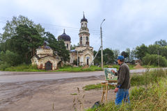 Male artist painting church on plein air. Male artist on painting on canvas in outdoor. Plein-air stock image