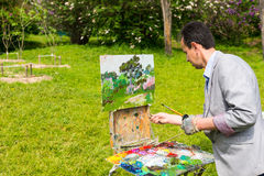Male artist painting outdoors. In the park  on a trestle and easel painting with oils and acrylics holding paintbrush and paletteknife wearing a glove Royalty Free Stock Image