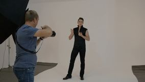 A male artist, he participates in a photo shoot. stock video footage